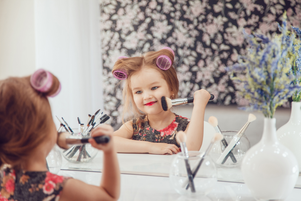 little girl putting make up on