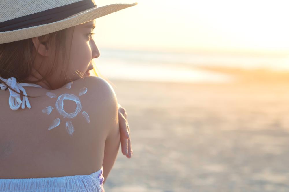 girl on beach with sunscreen