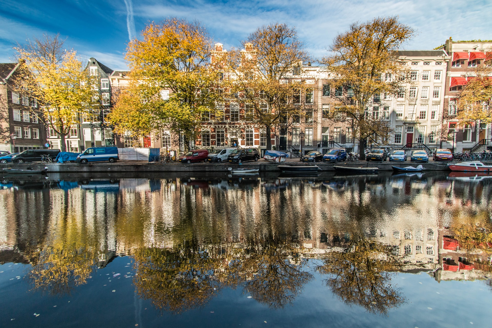 Buildings and trees near a water body with boats in Amsterdam