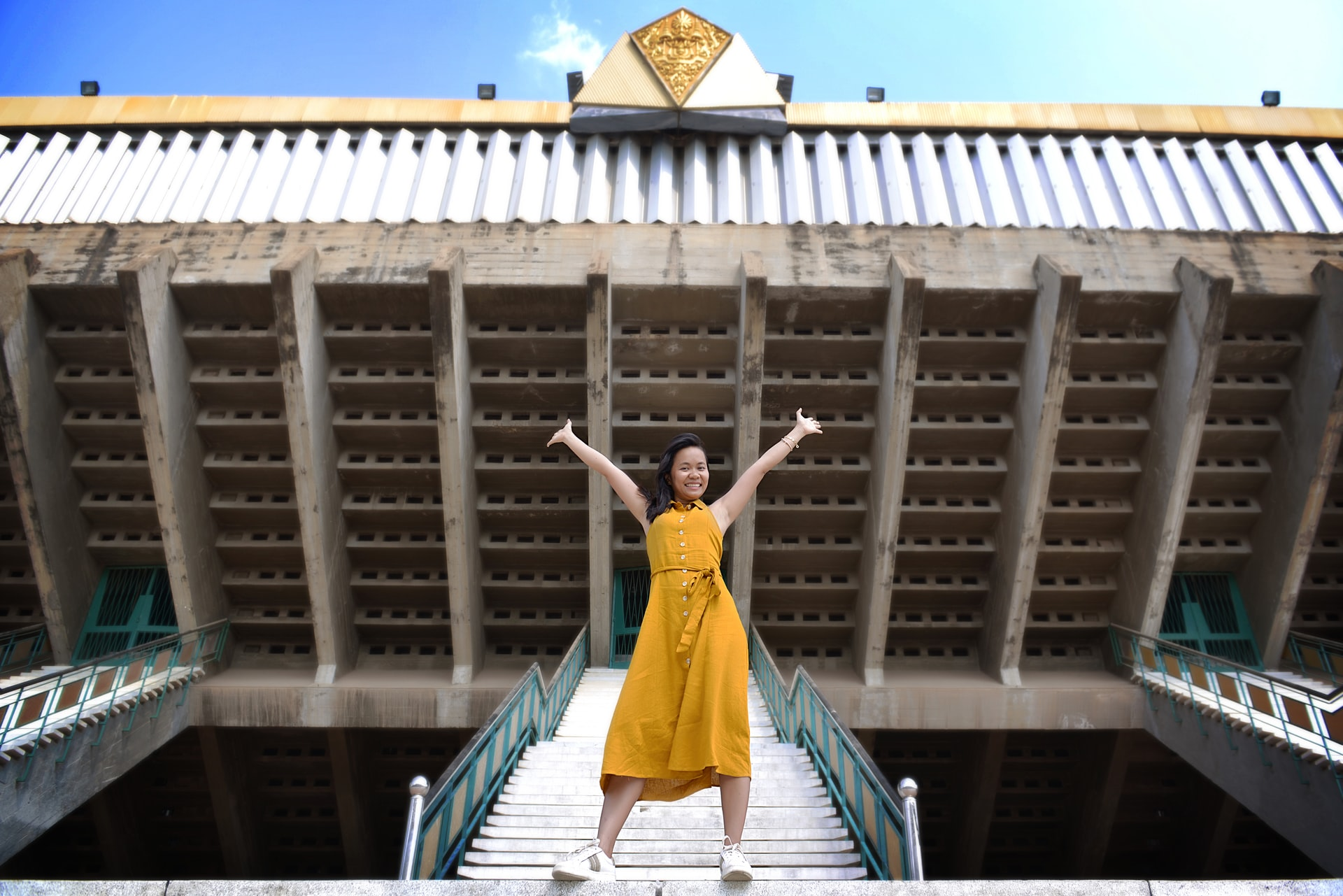 Girl in yellow dress standing on stairs with outstretched arms