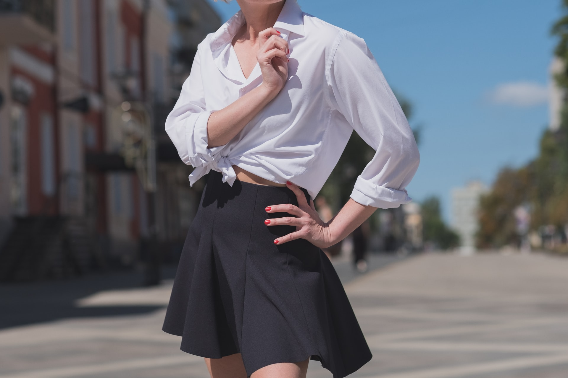 female wearing a short black skirt and a white blouse