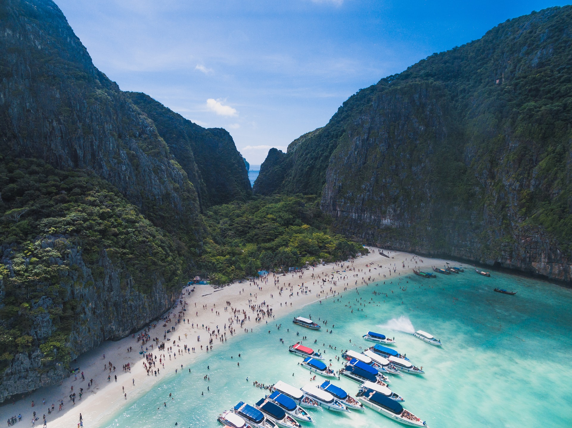 an aerial view of Maya Bay in Thailand with several boats in the water and a crowd on the beach