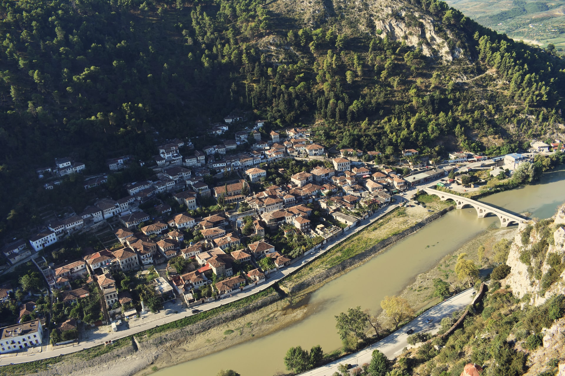 an aerial view of the city of Berat showing a river, a bridge and houses along the hillside
