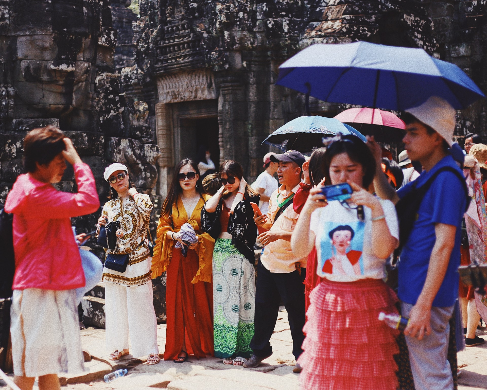Group of tourists standing outside a temple in Cambodia. Some are adjusting their clothes, some are taking photos, while some are standing under the shade of umbrellas.