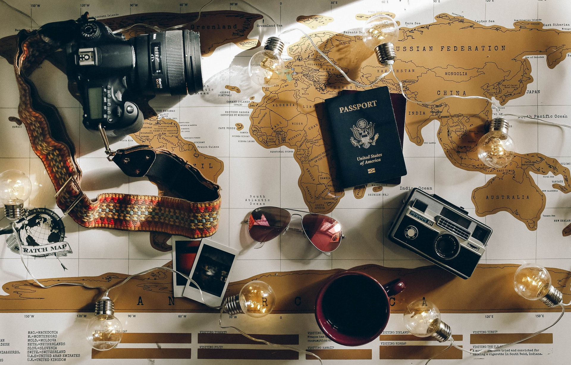 a digital camera, two polaroid photos, a passport, sunglasses, a film camera and light bulbs placed on top of a brown and white map