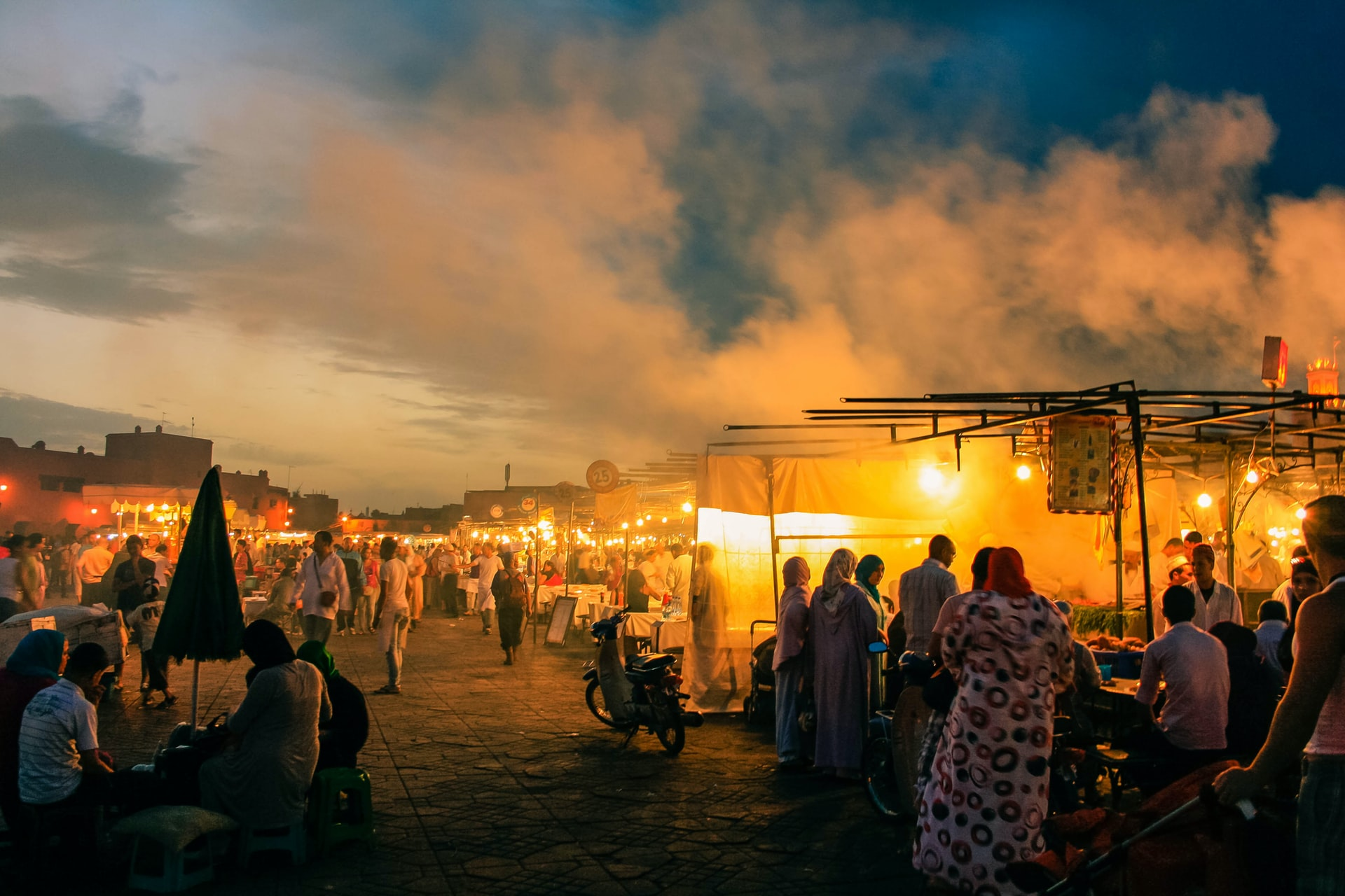 Busy market with stalls and people in the sunset in Marrakech