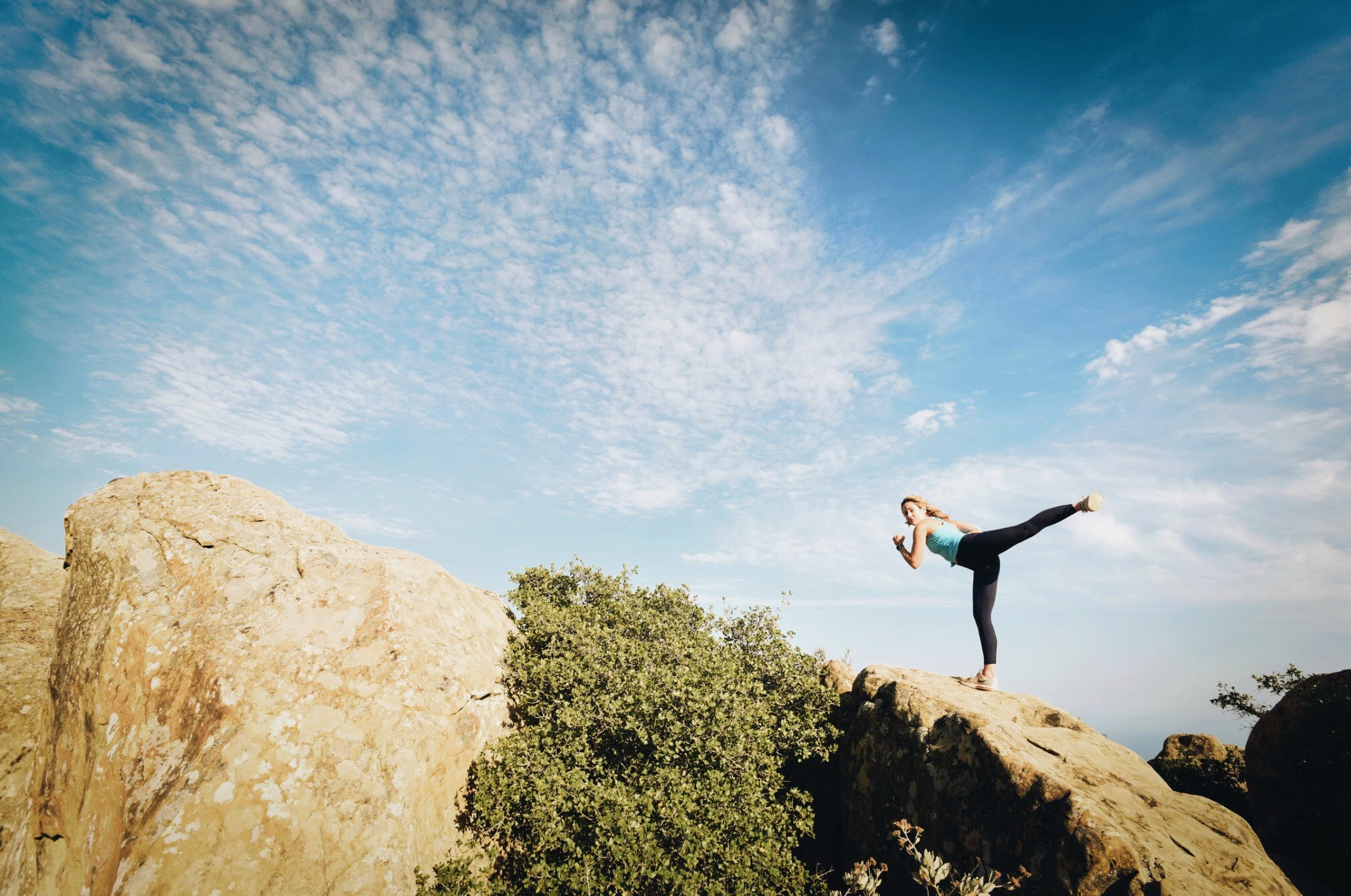 Woman exercising on top of a rock