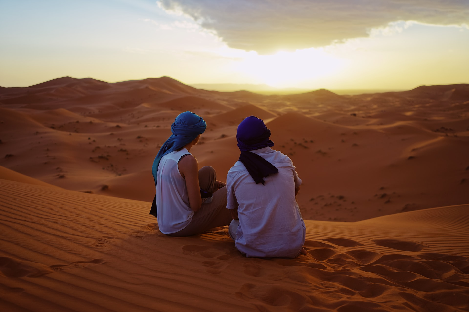 Man and woman with head gear looking at a sunset over a desert in Morocco.