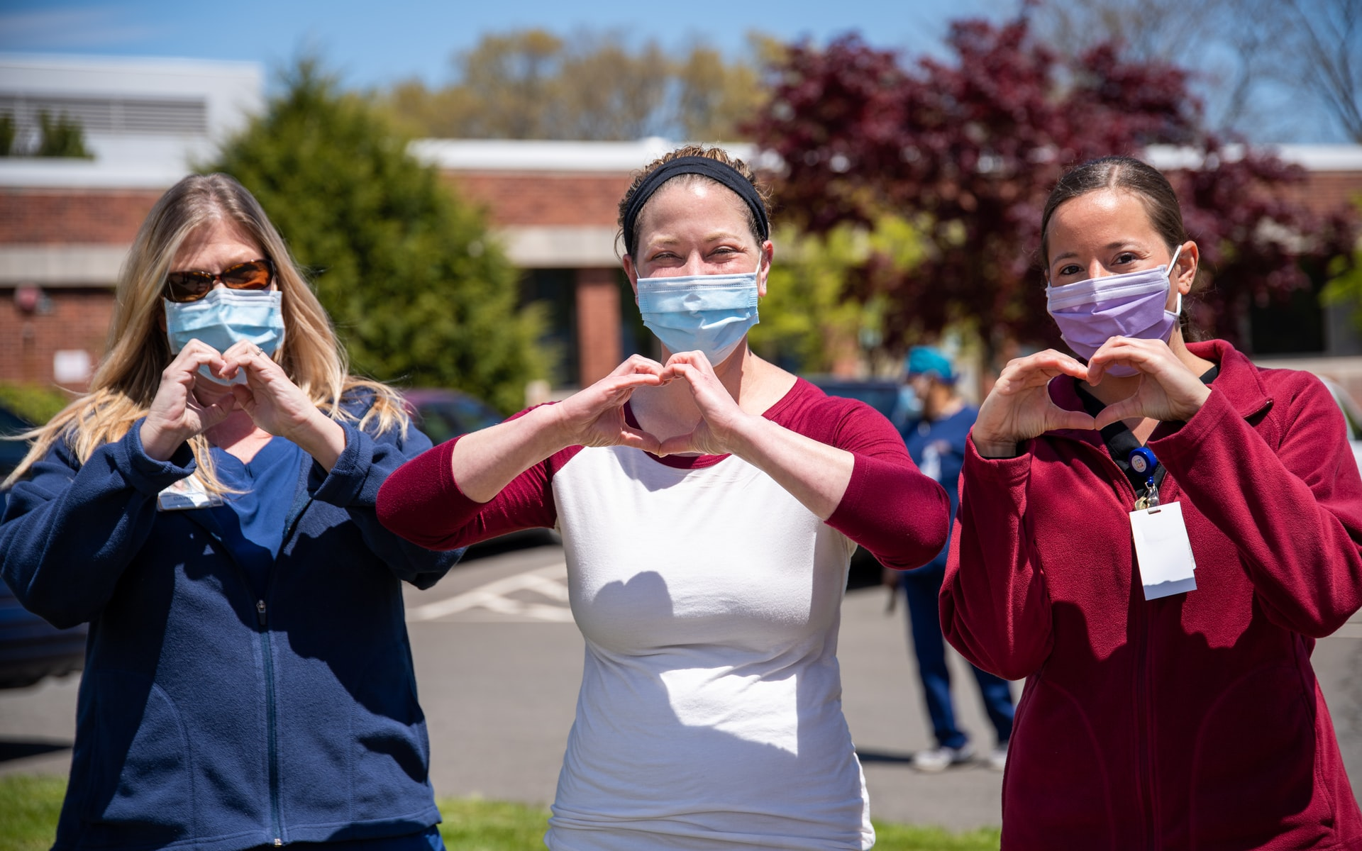Three females wearing masks making a heart shape with their hands