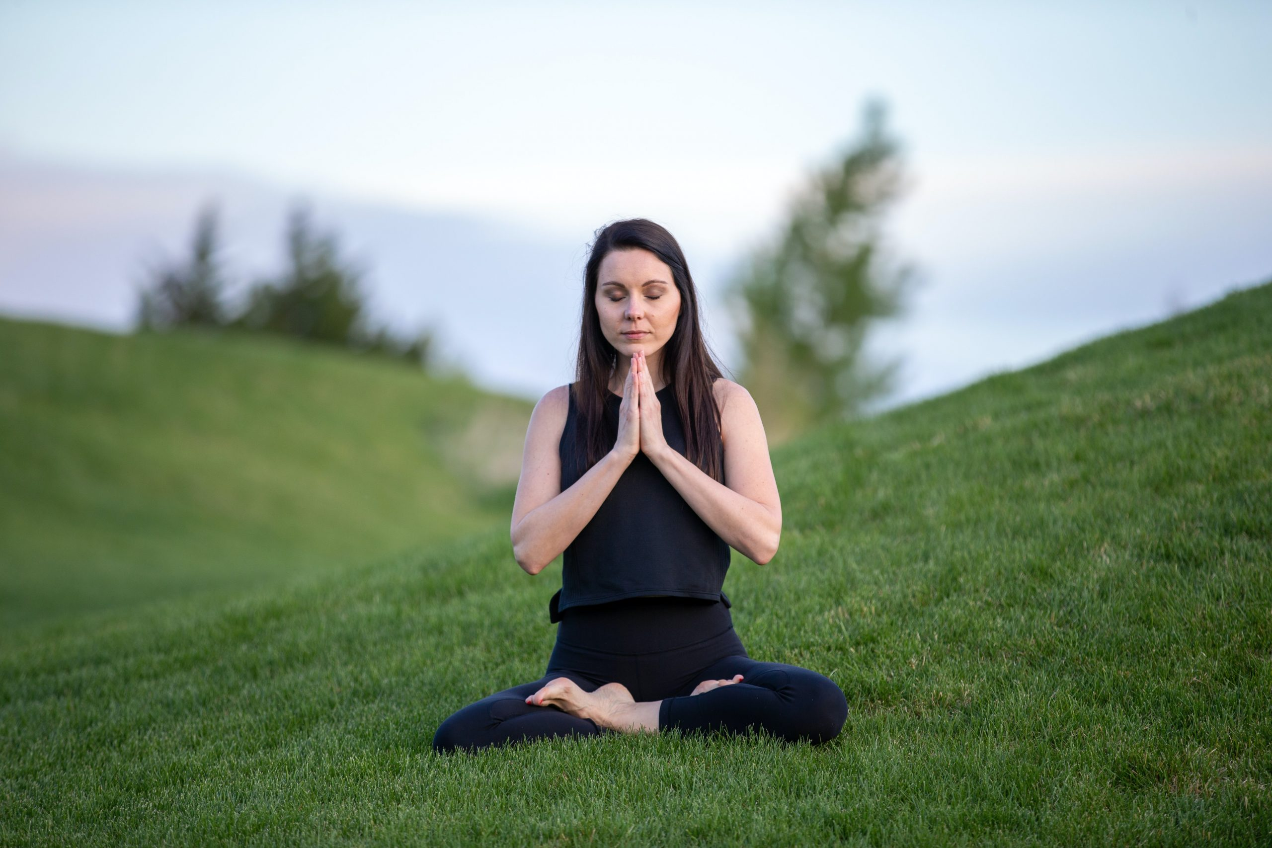 Woman wearing a black outfit sitting crosslegged with folded hands and closed eyes, sitting outdoors