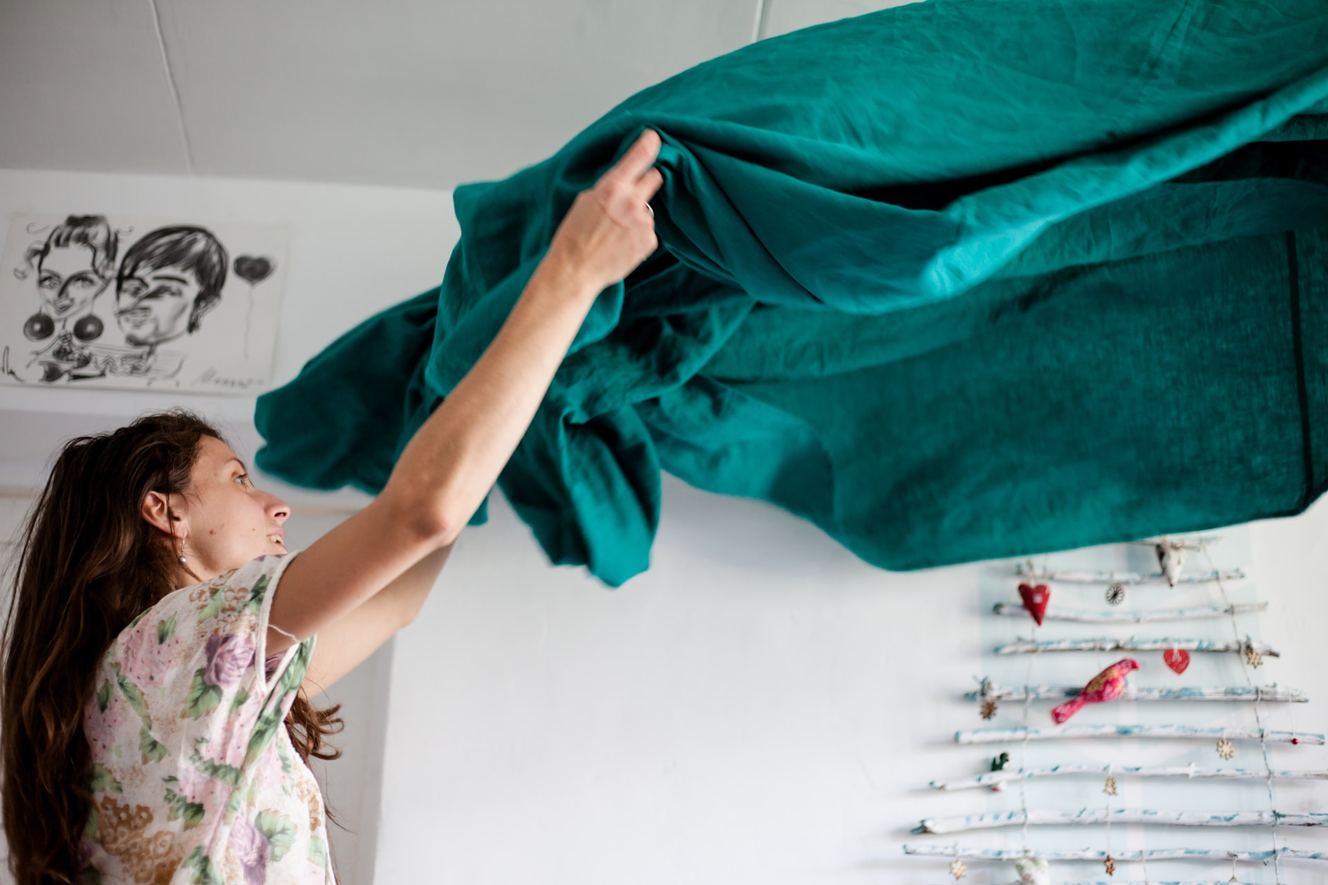 Woman airing out a green bedsheet