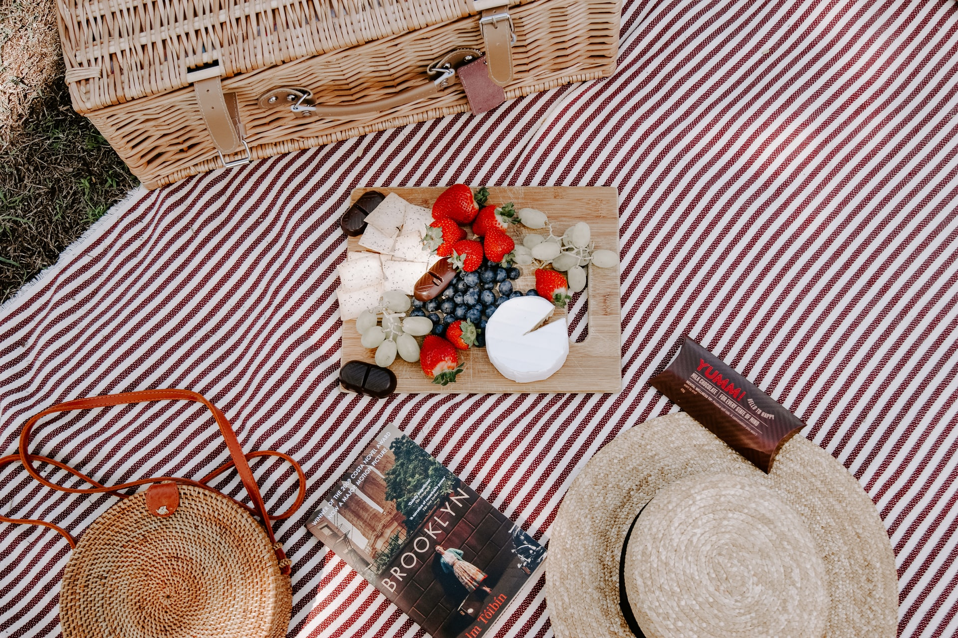 Picnic basket, book, hat and flowers laid out on a red and white cloth