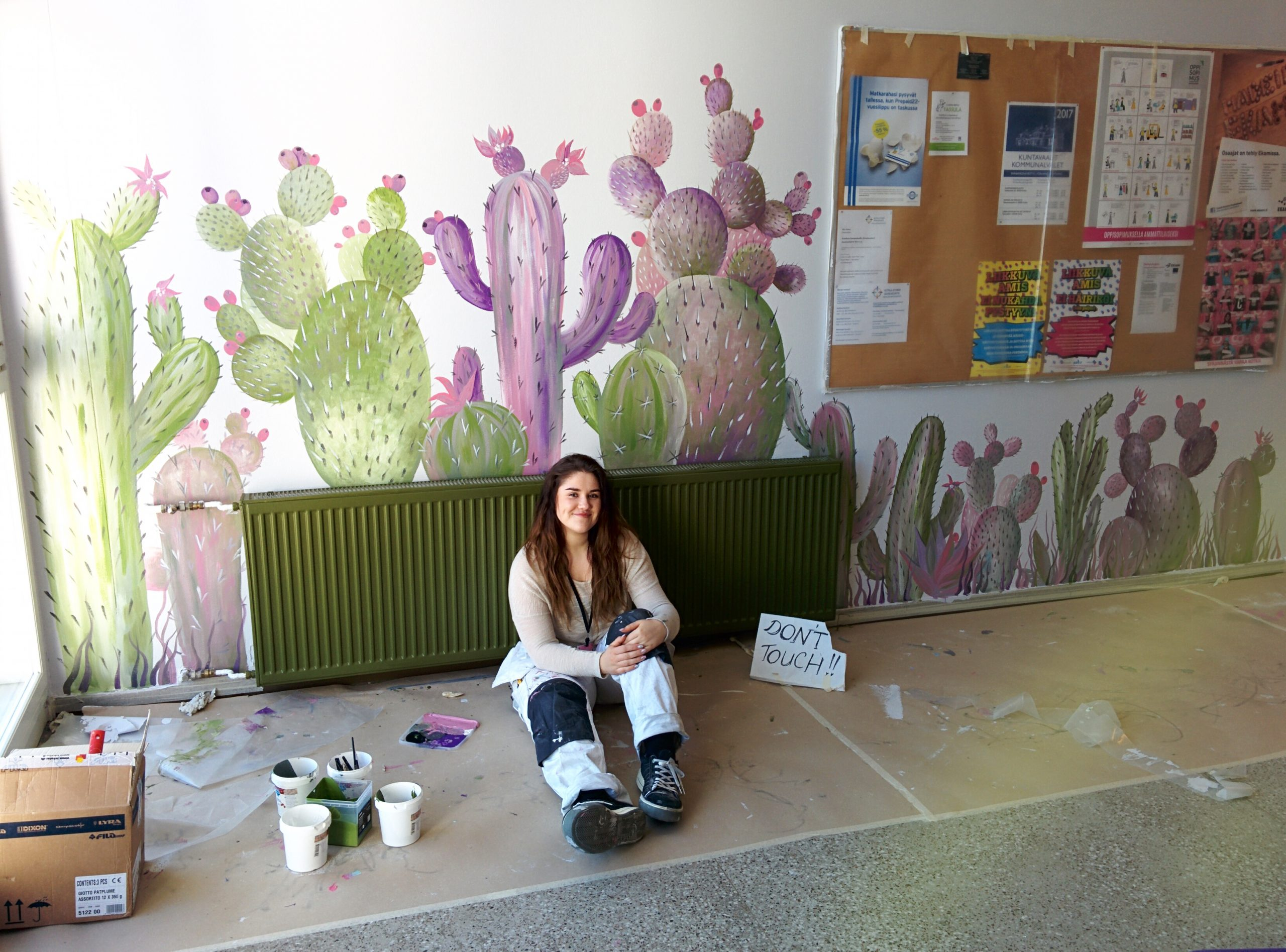 Ocean sitting on the floor near a wall painted with blue and purple cacti