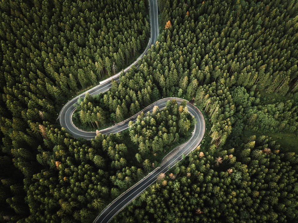 Aerial,View,Of,Countryside,Road,Passing,Through,The,Green,Forest