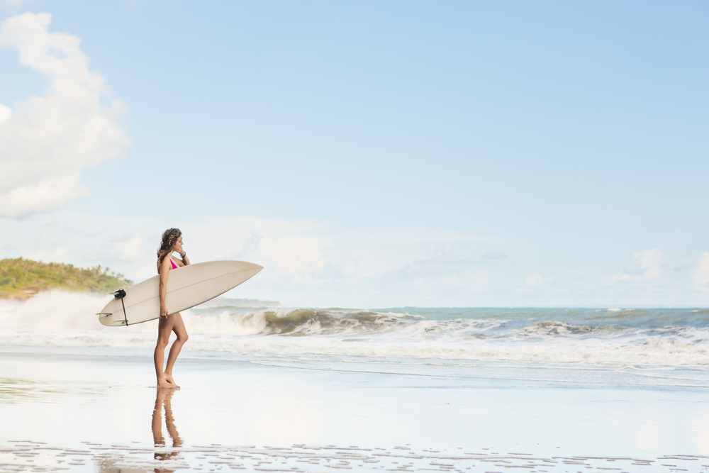woman holding surf board on the beach